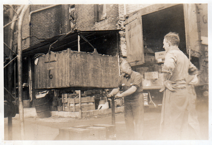 Charles B. Johnson unloading an industrial battery for repair (1952)