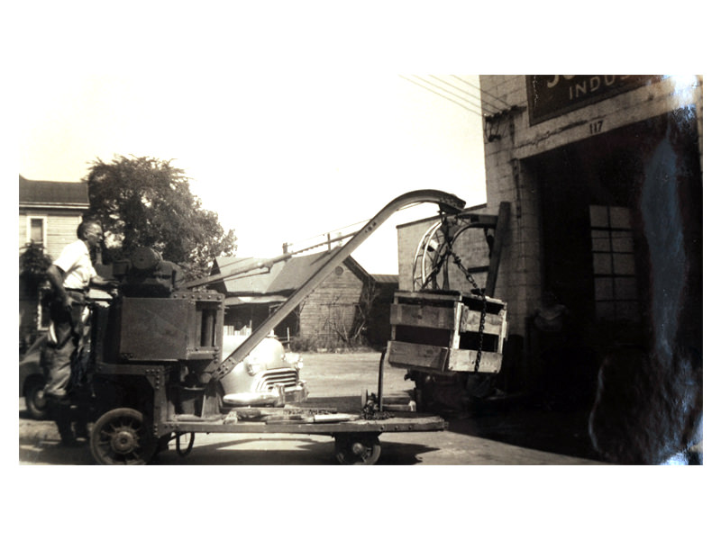 Charles B. Johnson using an electric crane to transport an industrial battery (1945)